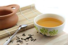 Tee in einer Schale und ein Tongefäß und ein Löffel Stockfoto