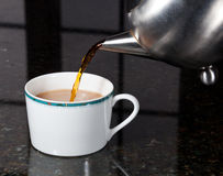 Tee gegossen aus Edelstahlteekanne Stockfoto