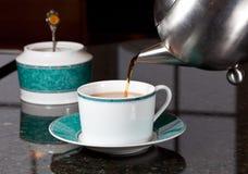 Tee gegossen aus Edelstahlteekanne Lizenzfreies Stockbild