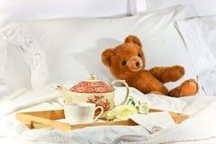 Tee im Bett mit Teddybären Stockbild