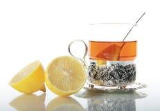Tee im Glasbecher und in den Zitronen Lizenzfreie Stockfotografie