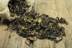 Tee im Sack des groben Sackzeugs auf hölzernem Lizenzfreies Stockfoto