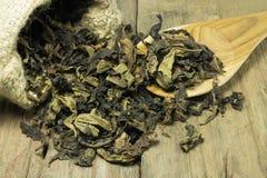 Tee im Sack des groben Sackzeugs auf hölzernem Stockfotografie