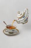 Tee läuft in ein Cup aus Stockfotos