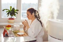 Tee-Lesetablette der Frau trinkende am Befeuchter Lizenzfreies Stockfoto