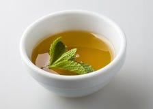 Tee lief herein eine weiße Schüssel aus Stockfotografie