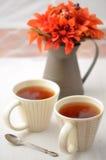 Tee mit Fallblumen Stockbild