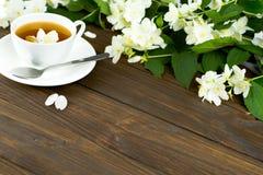 Tee mit Jasmin in einer weißen Schale auf einem Holztisch Stockfotografie