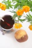 Tee mit Muffin und einem globeflower lizenzfreie stockbilder
