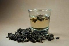 Tee mit Oolong im Glas auf braunem Hintergrund Lizenzfreie Stockbilder