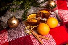 Tee mit Orange, Orangen, Plaidplaid, Zimt auf dem Hintergrund eines Weihnachtsbaums im neuen Jahr Lizenzfreies Stockfoto