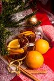 Tee mit Orange, Orangen, Plaidplaid, Zimt auf dem Hintergrund eines Weihnachtsbaums im neuen Jahr Lizenzfreie Stockbilder