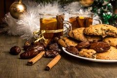 Tee mit Orange, Plaidplaid, Zimt auf dem Hintergrund eines Weihnachtsbaums im neuen Jahr Stockbilder