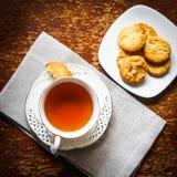 Tee mit Plätzchen auf hölzernem Hintergrund Stockbild