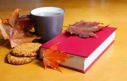 Tee mit Plätzchen, Buch und Herbstlaub Selektiver Fokus Lizenzfreie Stockfotografie