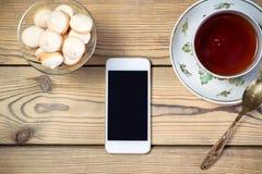 Tee mit Snack und Handy auf Holztisch Stockfotografie