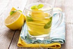 Tee mit tadelloser und ganzer Zitrone in einer transparenten Schale Stockbild