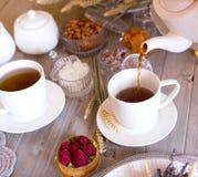 Tee mit weißen Schalen und Kuchen lizenzfreie stockfotos