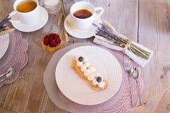 Tee mit weißen Schalen und Kuchen stockbild