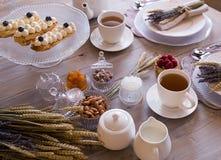 Tee mit weißen Schalen und Kuchen stockbilder