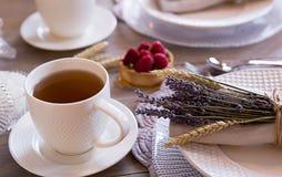 Tee mit weißen Schalen und Kuchen lizenzfreie stockfotografie
