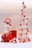 Tee mit Weihnachtsbaum und gestricktem Schneemann Lizenzfreie Stockbilder