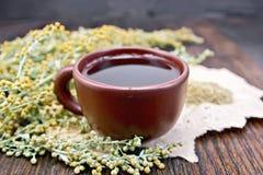 Tee mit Wermut in der Lehmschale an Bord lizenzfreie stockfotografie