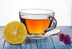 Tee mit Zitrone und Blume auf einem hölzernen Hintergrund Stockbild