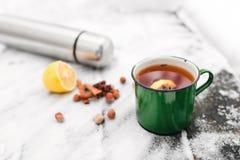 Tee mit Zitrone und Kardamom auf dem Hintergrund einer schneebedeckten Tabelle Stockfotografie