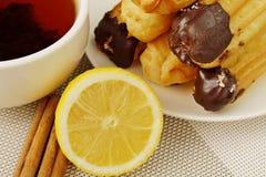 Tee mit Zitrone Zimt und Eclairs lizenzfreie stockfotos