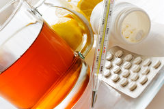 Tee mit Zitronen und Grippepillen mit Thermometer - grippe Abhilfe Stockbild