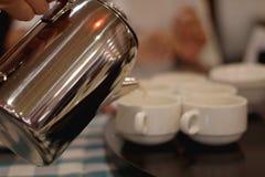 Tee oder Kaffee wird in die Schale gegossen lizenzfreie stockbilder