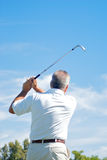 Tee Off. A golfer holding his finish after a good shot. Nice clean blue sky Stock Images