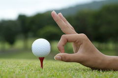 Tee off. Hand and golf ball on tee Stock Image