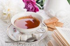 Tee, Plätzchen, das Buch und Pfingstrosen Stockbilder