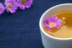 Tee-Schale und Violet Flowers auf dunkelblauem Tischdecken-Hintergrund lizenzfreies stockfoto