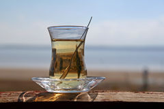 Tee by the sea. A glass of turkish tea by the sea Royalty Free Stock Image