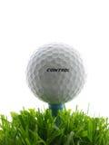 Tee Shot. Golf ball  on tee, in the grass. Word control written on ball Stock Photo