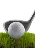Tee Shot. Golf ball on a tee in grass about to be struck by a golf club Stock Photography