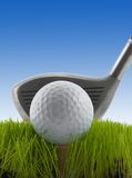 Tee Shot. Golf ball on a tee in grass about to be struck by a golf club Stock Photos