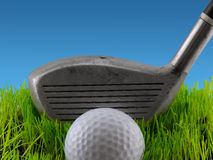 Tee Shot. Golf ball on a tee in grass about to be struck by a golf club Royalty Free Stock Image