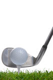 Tee shot iron. Close up of a golf ball on a tee with an iron club behind, studio shot using real grass royalty free stock photos
