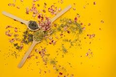 Tee stieg, Kamille und Thymian in einem hölzernen Löffel auf einem gelben Hintergrund stockfotografie