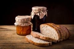 Tee und Brot mit Orangenmarmelade auf hölzernem Hintergrund Stockbilder