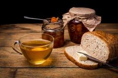 Tee und Brot mit Orangenmarmelade auf hölzernem Hintergrund Lizenzfreie Stockfotos