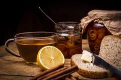 Tee und Brot mit Orangenmarmelade auf hölzernem Hintergrund Lizenzfreie Stockbilder