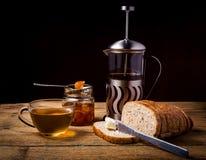 Tee und Brot mit Orangenmarmelade auf hölzernem Hintergrund Stockfoto