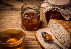 Tee und Brot mit Orangenmarmelade auf hölzernem Hintergrund Stockfotografie