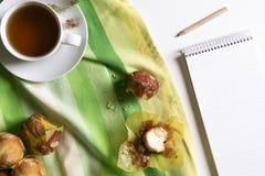 Tee und Muffins und leeres Notizbuch lizenzfreie stockfotografie
