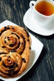 Tee und selbst gemachte Bäckerei mit Schokolade auf dunklem Holztisch Stockbild